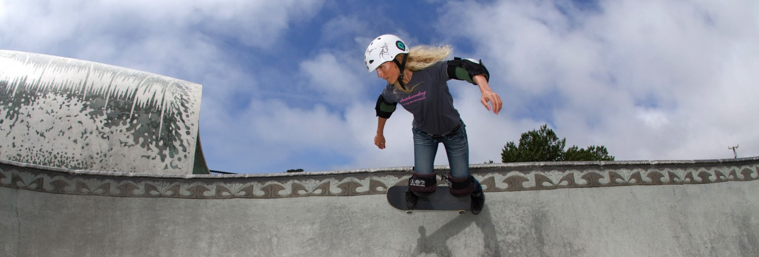 Barbara Odanaka performs a kick-turn on a skateboard, at a skateboard park. The tops of a tree and a utility pole are visible in the background, beneath a cloudy, blue sky.